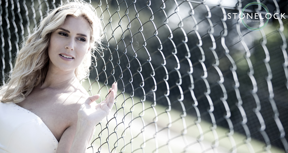 A bride leans against a wire fence and gazes into the distance