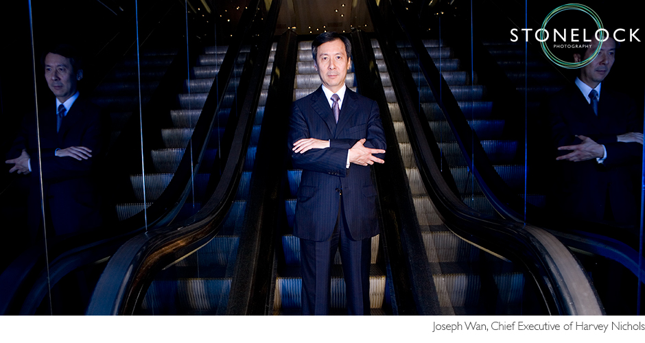 Joseph Wan the chief executive of Harvey Nichols stands with his arms folded at the bottom of the escalators in the store