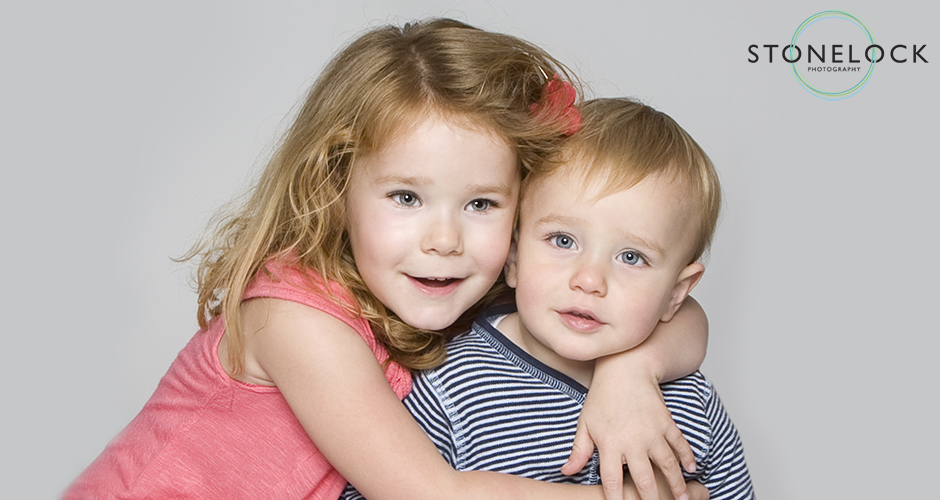 Brother and sister hug, they are sitting in a photographic studio on a pale grey background