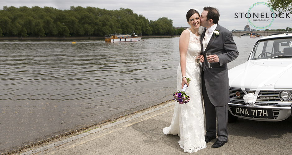 A bride and groom stand by the wedding car by the River Thames in Putney