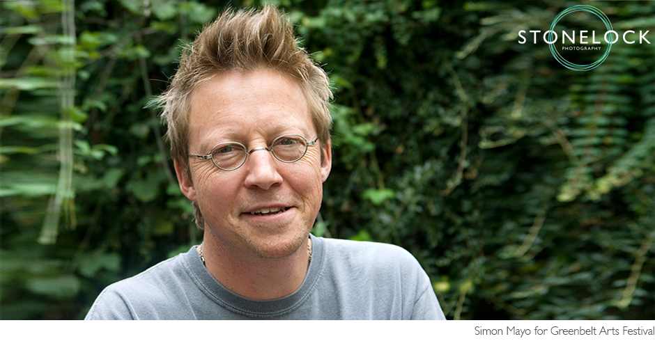 Simon Mayo poses in front of some greenery for a closely cropped headshot