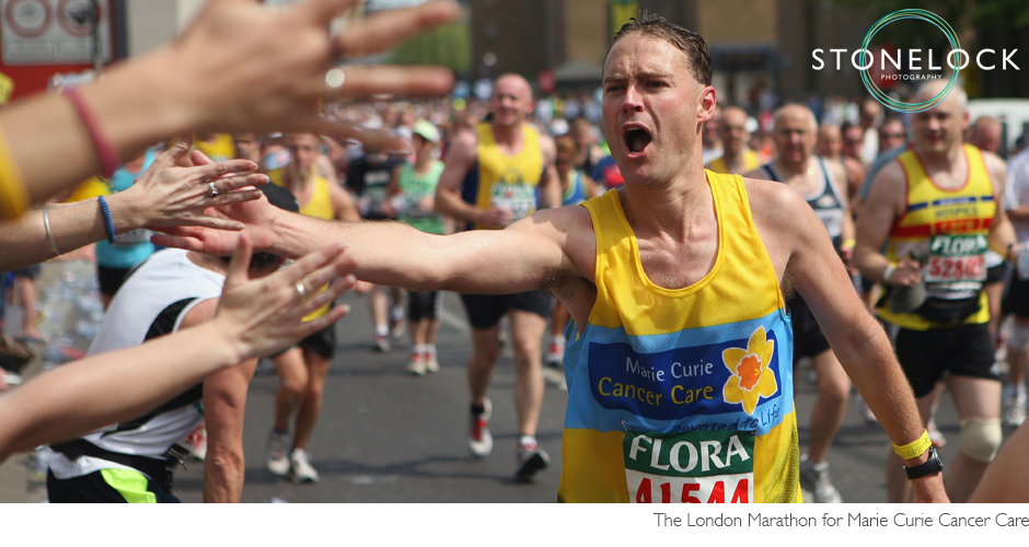 A runner for Marie Curie Cancer Care reaches out to slap supporters hands as he runs in the London Marathon