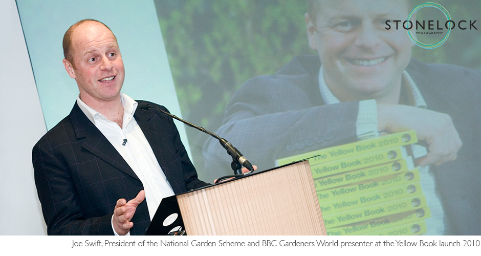 Joe Swift the BBC TV presenter stands at a lectern and makes a speech at the launch of the National Garden Scheme's yellow book