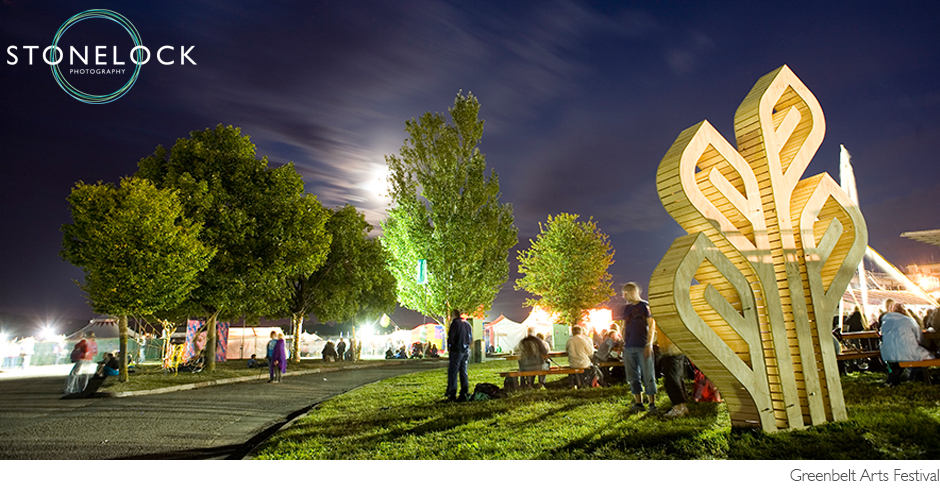 Greenbelt Arts Festival at Cheltenham racecourse at nighttime, shot on a slow shutter speed there is movement blur as people walk around