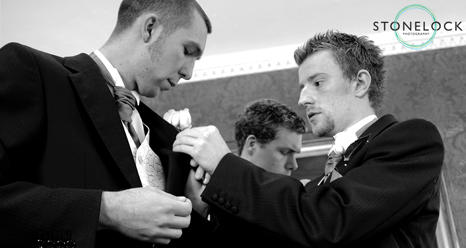 A groom pins the button hole onto his best mans jacket
