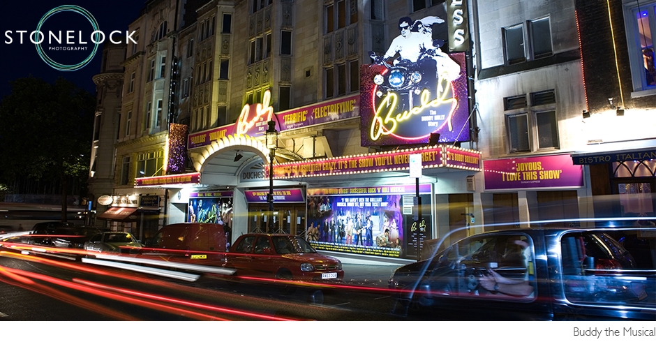 The Duchess Theatre in London lit up for the Buddy Holly Story shot at nighttime there dis a trail of car lights swiping past