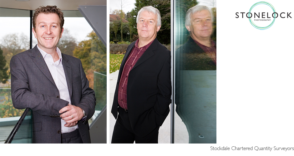 Portraits of two business men, one leans against a glass door and is reflected, the other leans on a glass wall