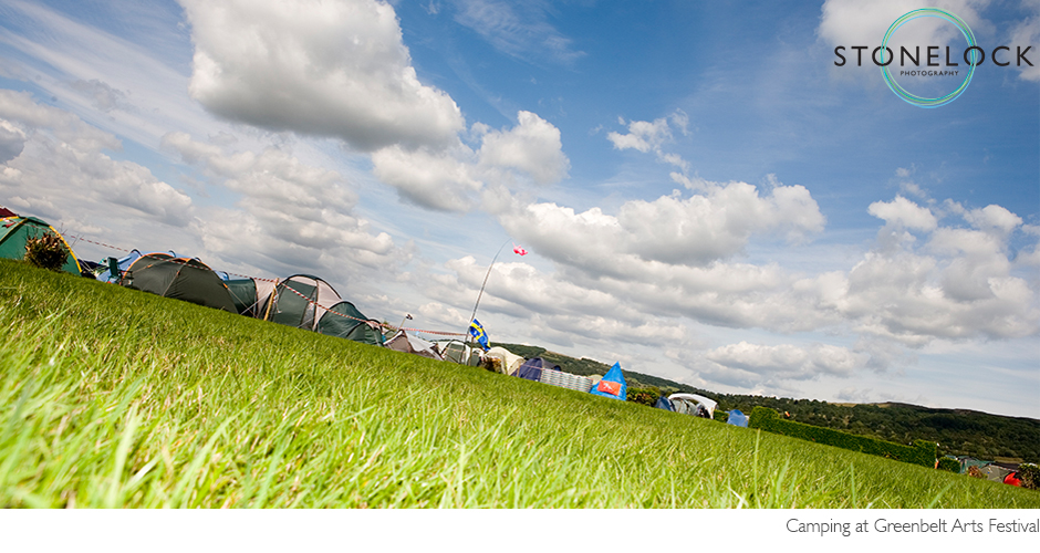 A campsite at Greenbelt Arts Festival, shot from low down there is grass, small tents in the background and lots of blue sky