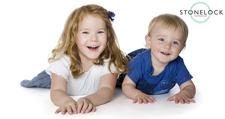 A four year old girl and her one year old brother lie on their stomachs in a photography studio and laugh at the camera