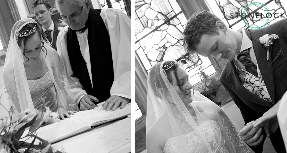 The bride and groom sign the marriage register with the vicar