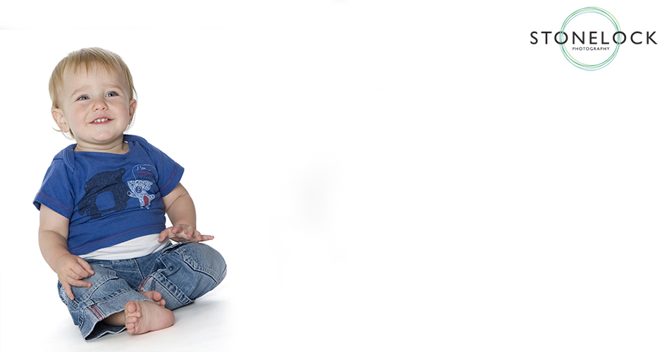 A one year old boy wearing blue sits on the floor in a photography studio and laughs