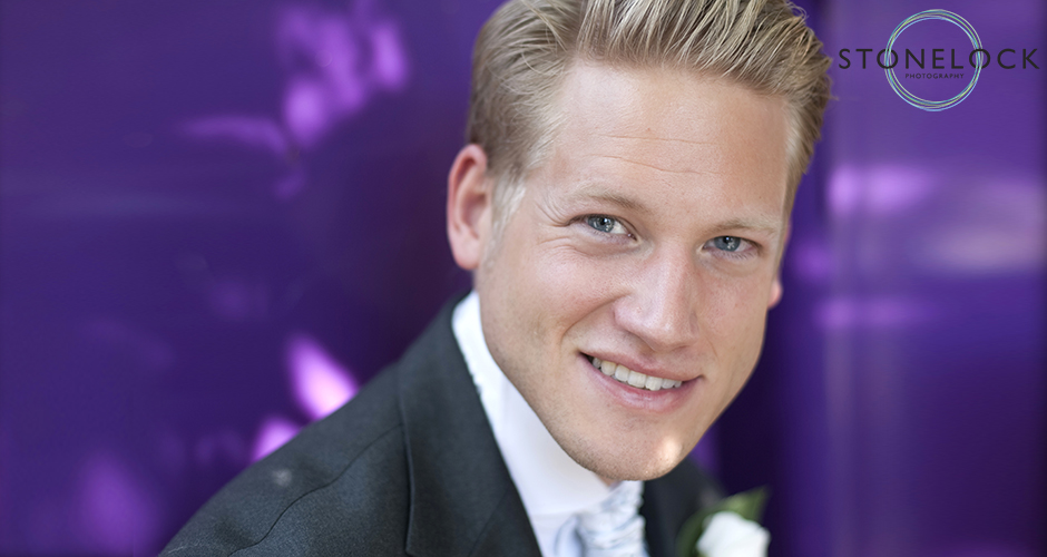 A groom poses for a portrait in front of a vivd purple background and smiles at the camera
