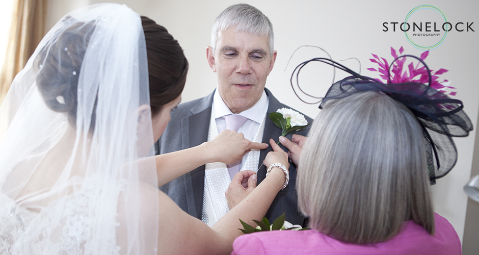 The bride and her mother pin the button hole onto her father's jacket