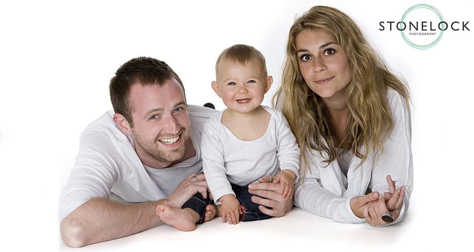 A family with a baby lie on their stomachs in a photography studio