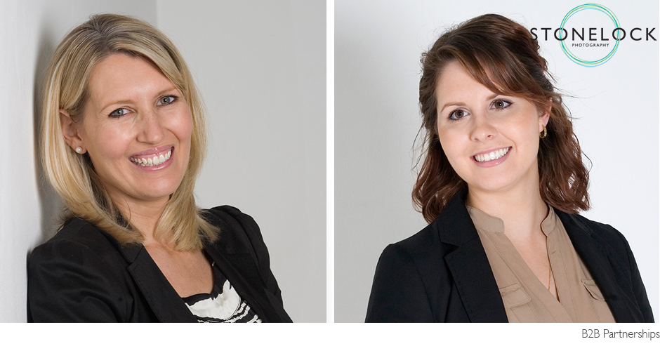 Two women in business suits pose for corporate portraits against a pale grey background