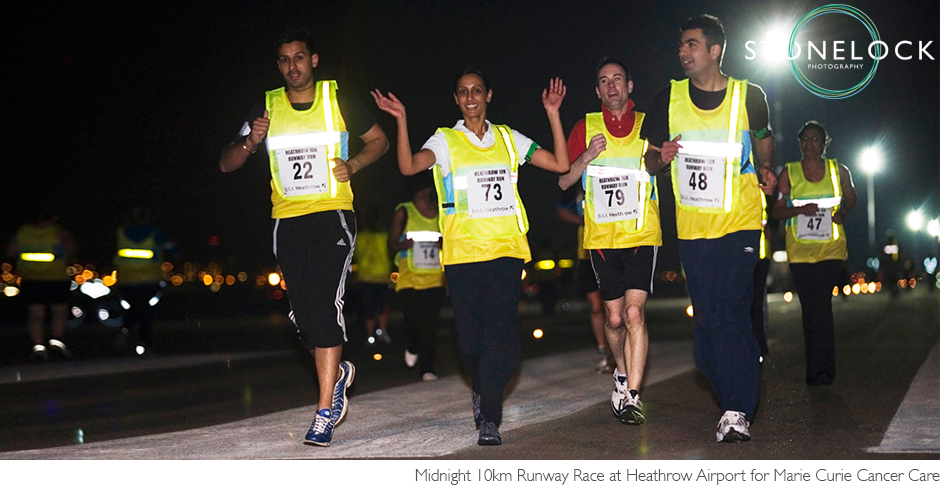 Runners wearing hi-vis vests run in the midnight run at Heathrow Airport to raise money for Marie Curie Cancer Care