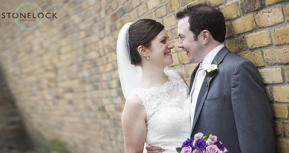 A bride and groom pose leaning against a yellow brick wall