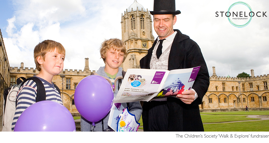 Two children receive directions form a guide at Oxford University, they are holding purple balloons