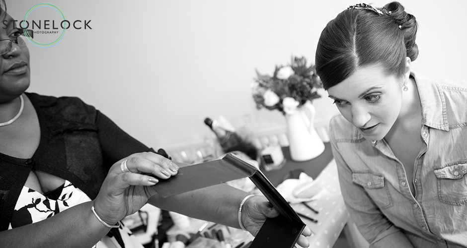 A bride checks her bake-up in a hand-held mirror as she gets ready for her wedding