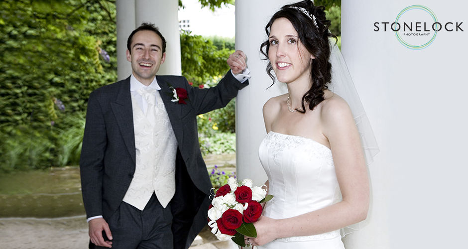 A bride poses as her husband stands in the background laughing