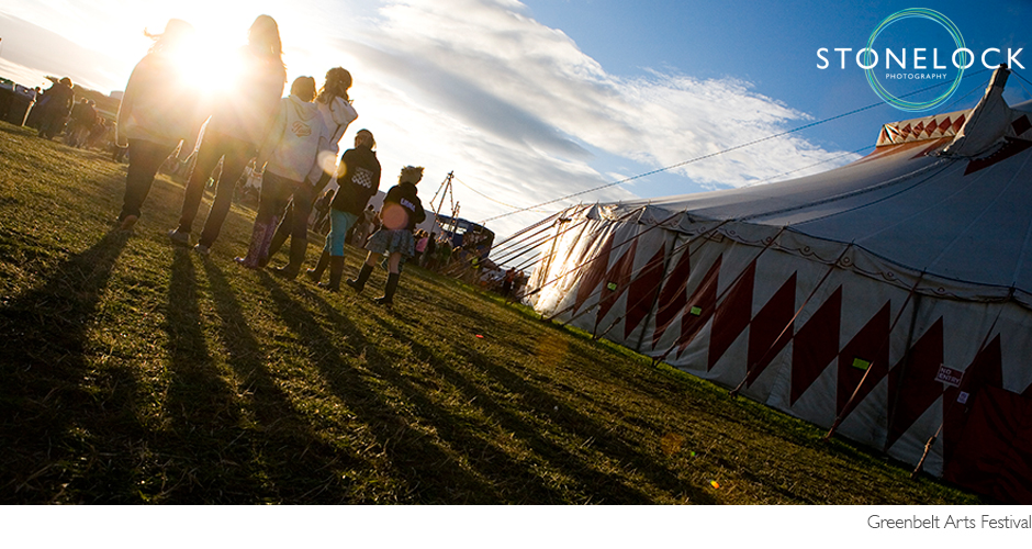 A group of people walk away from the camera into the sunset at Greenbelt Festival. A big top tent sits to the right hand side.