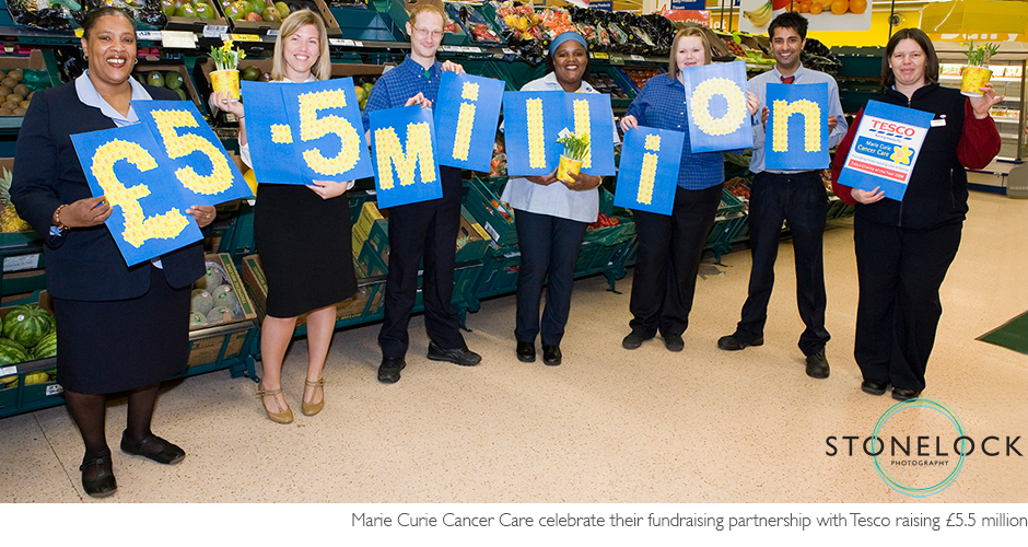 Staff from Tesco's celebrate raising 5.5 million punds for Marie Curie Cancer Care by holding up the numbers in front of the fruit and vegetable aisle