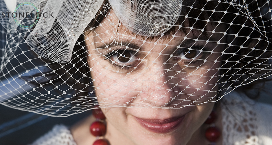 A bride with large eyes piers through the veil attached to her hat and up at the camera