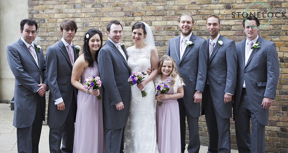 The wedding party with bride and groom, best man, ushers and bridesmaids stand in front of a yellow brick wall