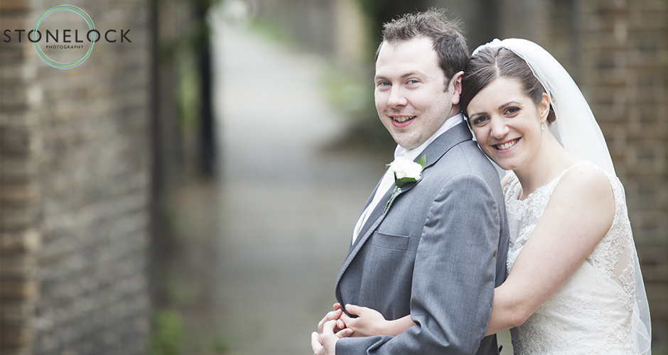 A bride stands behind her husband and leans her head on his shoulder