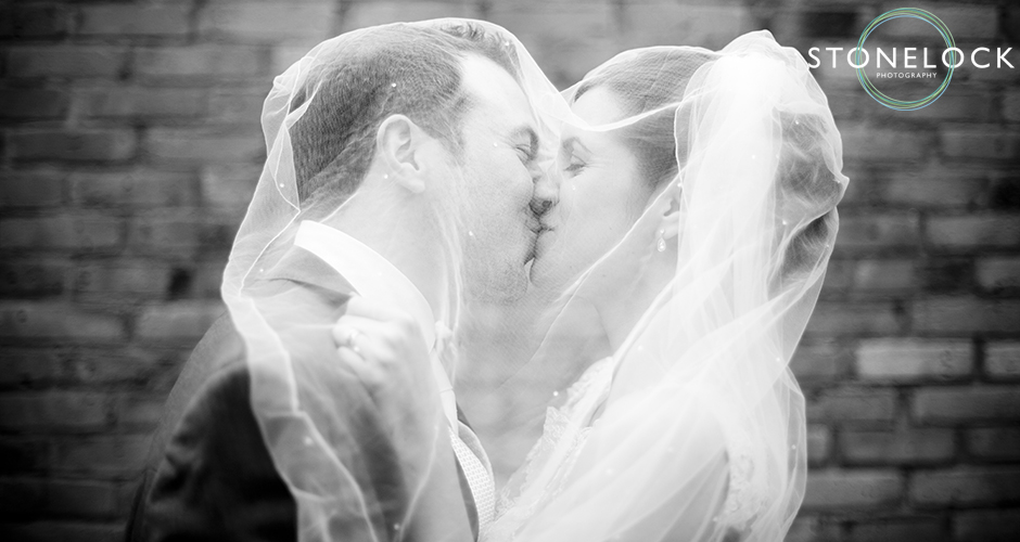 The bride and groom kiss under her veil