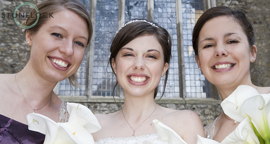 A bride with her two bridesmaids stand closely together and smile into the camera