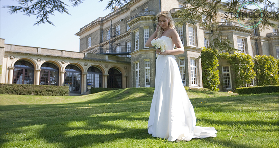 A bride stands outside the stately home, holding her hair out of her eyes she gazes down at her flowers
