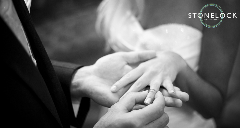 The groom places the ring onto his brides finger