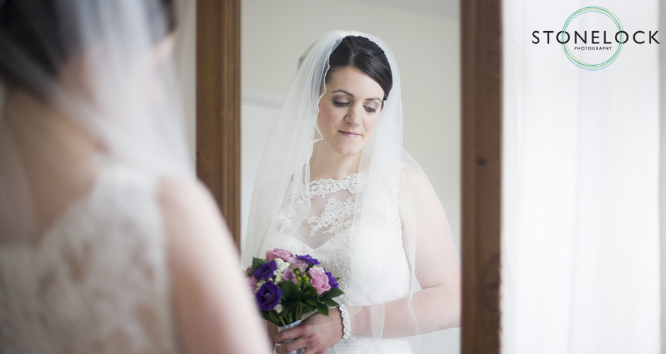 A bride stands in front of a mirror to show the front and back of her dress
