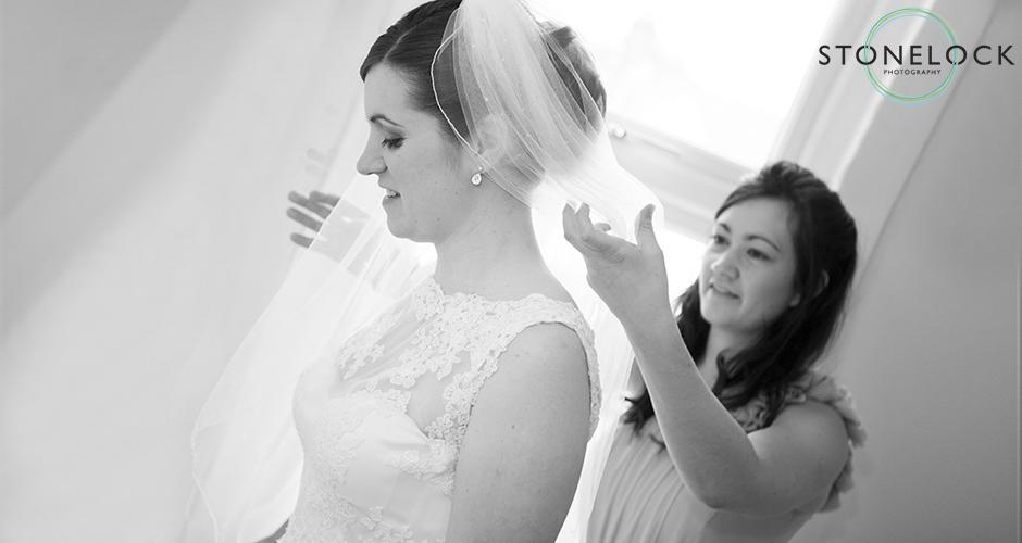 A bridesmaid helps the bride adjust her veil