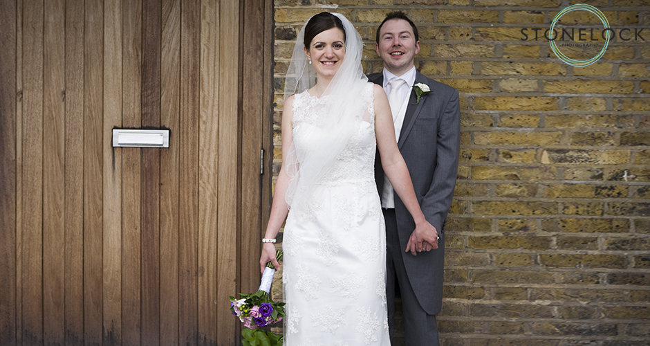 The bride and groom pose, leaning against a yellow brick wall