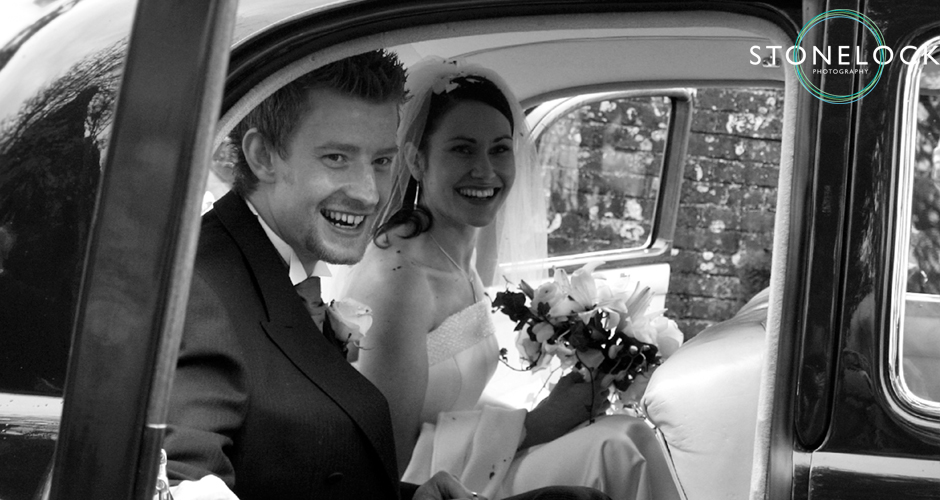 The bride and groom, just married, sit inside the wedding car