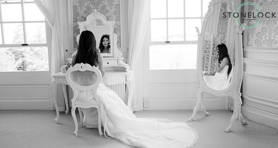 The bride sits at her dressing table and looks into the mirror, pausing just before she finishes getting ready for her wedding