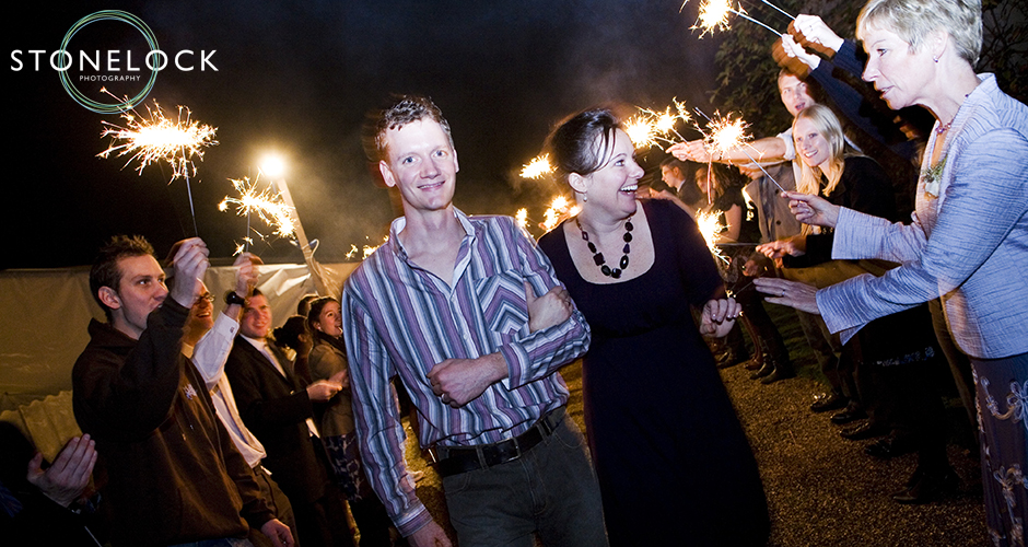 The bride and groom leave their wedding to fireworks and sparklers