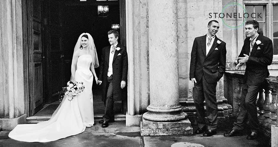 A bride and gorrom stand relaxed outside the church with the best man and an usher looking on