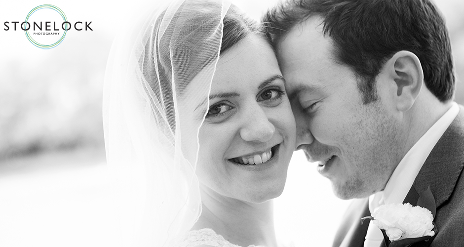 A groom rests his forehead on his brides head as she looks towards the camera and smiles
