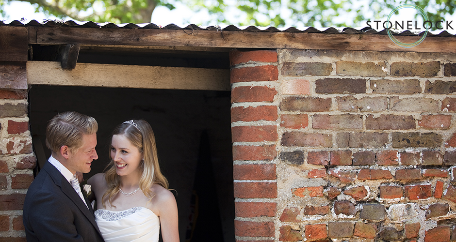 A bride and groom stand in the door way to an outbuilding against a background a rich red brick and green leaves