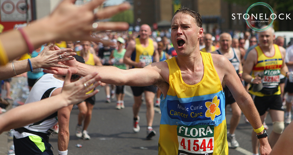 A runner for Marie Curie at the London Marathon reaches out to hit supporters hands as he runs past