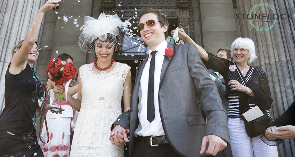 A bride and groom walk out of the registry office to a storm of confetti