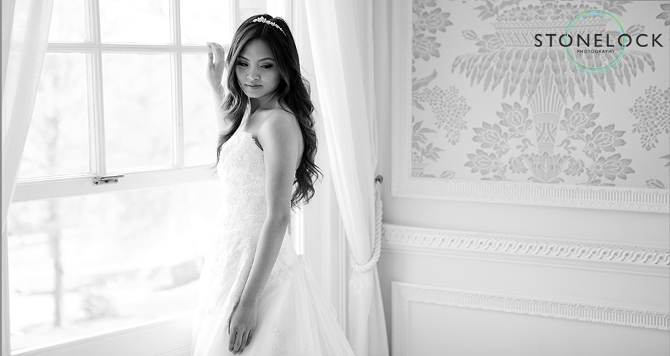 A bride before her wedding stands by the window and looks over her shoulder showing off her dress