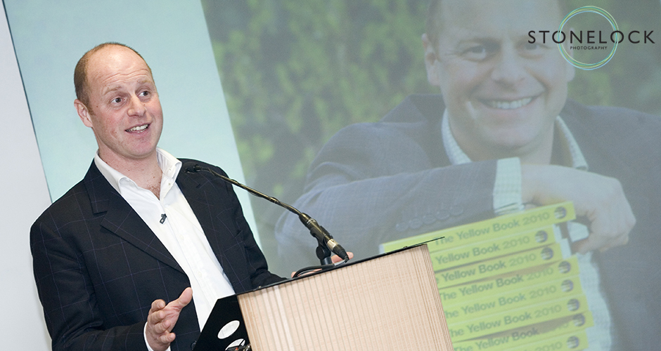 The BBCs Joe Swift stands on stage at a lectern and speaks the the launch of the National Garden Schemes Yellow Book