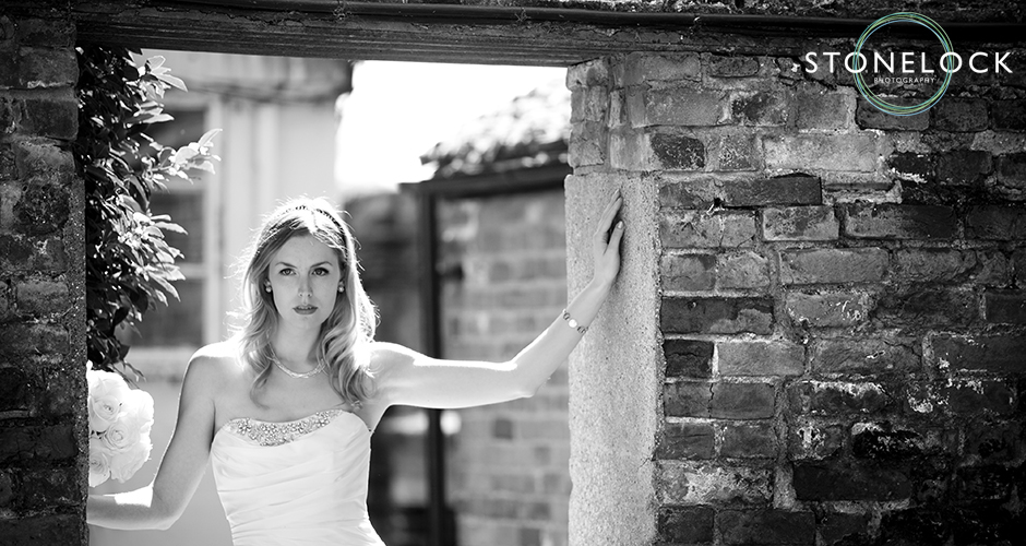 A bride with attitude stands in a garden doorway, hands resting on the frame and pouts