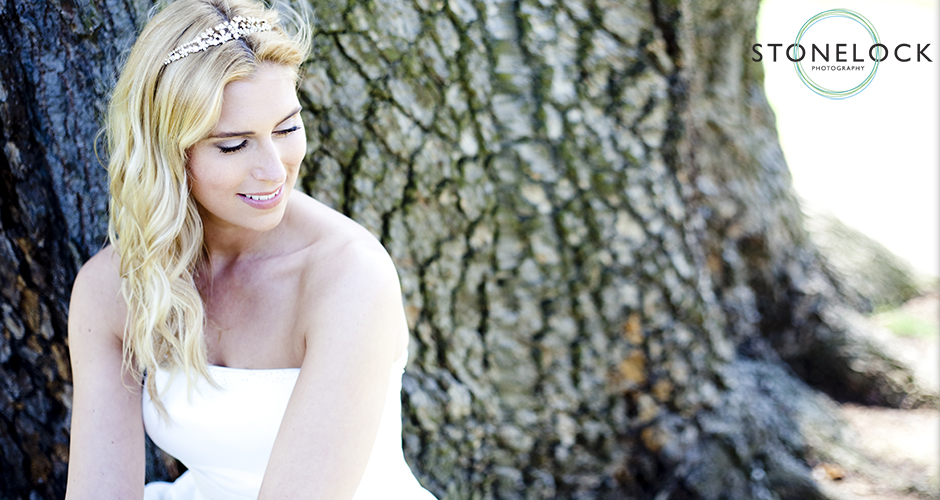 A bride sits outside by a tree and gazes down