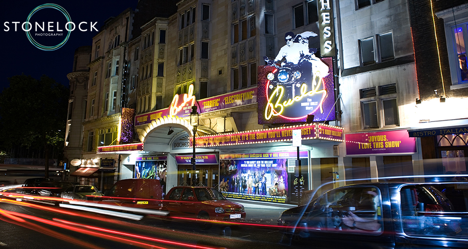 The Duchess Theatre in London lit up for The Buddy Holly Story shot at nightie there is a trail of car lights swiping past