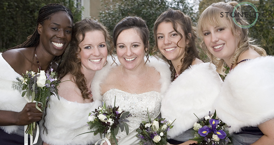 A bride and her four adult bridesmaids stand close together at a winter wedding